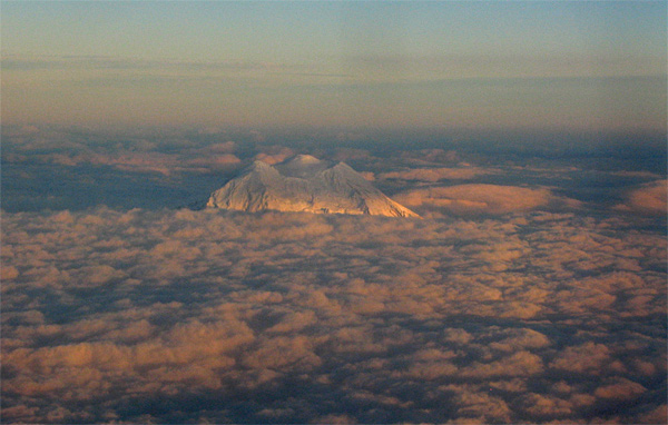 Lit by the setting sun, the top of Mount St. Helens looks like the top of an iceberg in a sea of clouds.