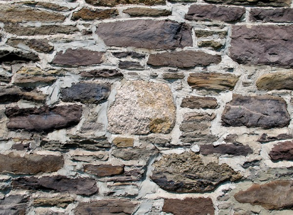 A piece of granitic fieldstone is incorporated into a wall.