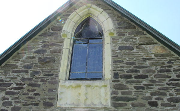 The end window illustrates the fine carving qualities of Caen stone. Note the great variety of other stone in this wall!