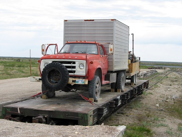 It is a challenge to get vehicles to and from Churchill. Here, the Manitoba Geological Survey's drill rig is loaded onto a flatbed car, for its travels on the Hudson Bay Railway.