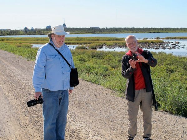 Michael Cuggy (L) and Dave Rudkin on the road, with the Churchill Northern Studies Centre on the horizon behind them.